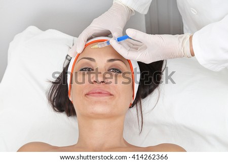 Young Woman Having Fillers Injection For Forehead Lines - stock photo