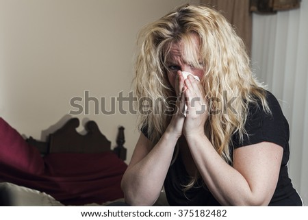 Young woman having flu, feeling bad, blowing her nose, - stock photo