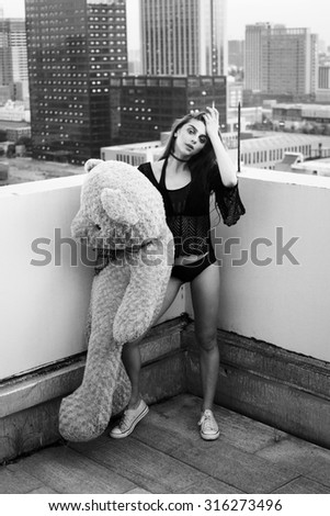 Young woman having fun,holding big soft teddy bear on rooftop and smoking.Party.Teen girl.Hipster.Black and white portrait.