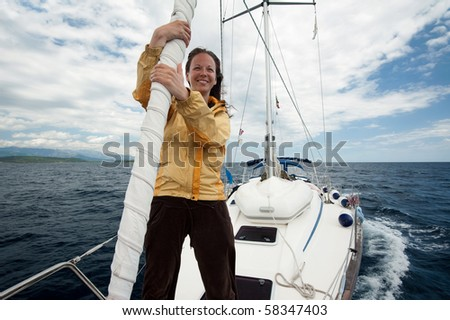 Young woman having fun on the front of a yacht - stock photo