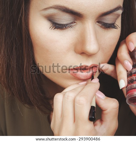 Young woman having make up applying by artist. Isolated on white background.