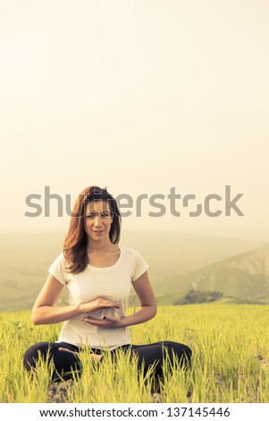Young woman having meditation at the mountain