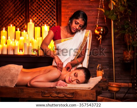 Young woman having oil Ayurveda spa treatment in India salon. - stock photo