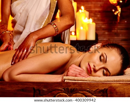 Young woman having oil Ayurveda spa treatment. Lighting candles. - stock photo