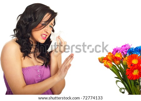 Young woman having spring flowers allergy sneezing and trying to stop flowers over white background - stock photo