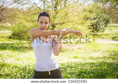 Young woman having stretching at the park