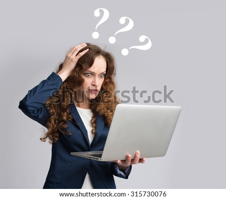 Young woman having trouble with laptop. Gray background - stock photo