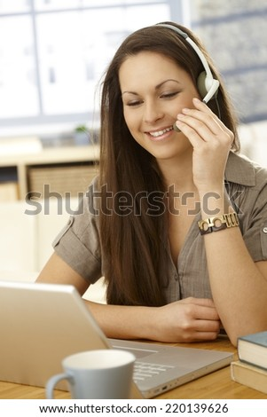 Young woman having video call, using laptop and headset, smiling. - stock photo