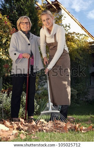 Young woman helping a senior with her garden - stock photo