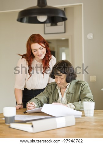 Young woman helping her Grandmother with paperwork