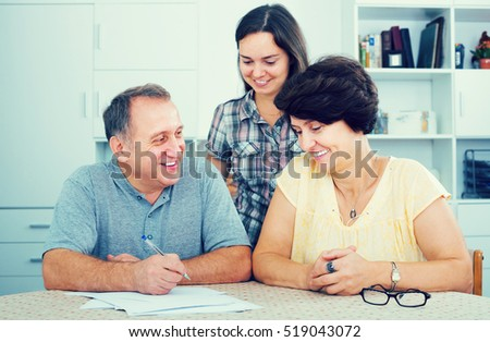 Young woman helping her mature  parents to do paperwork at home