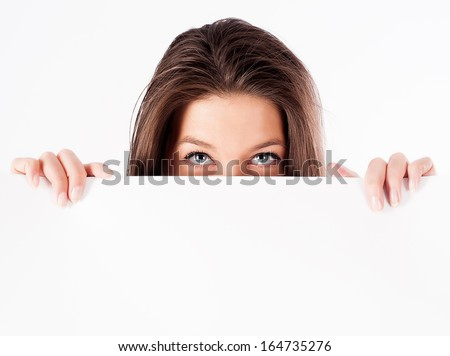 Young woman hiding behind a billboard and looking at camera. isolated on white background - stock photo
