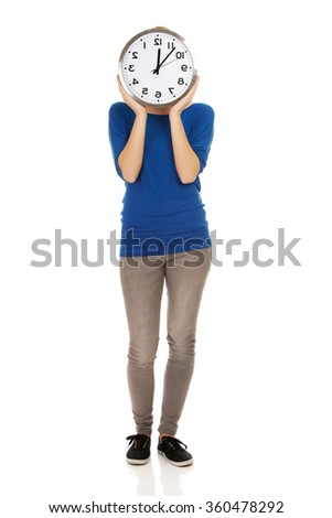 Young woman hiding behind a clock. - stock photo