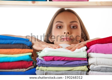young woman hiding behind a shelf with clothing, isolated on white background