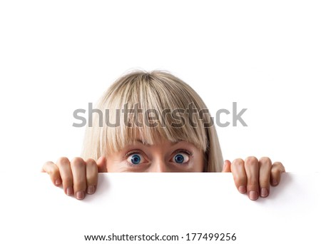Young woman hiding behind blank white board with surprised look. - stock photo