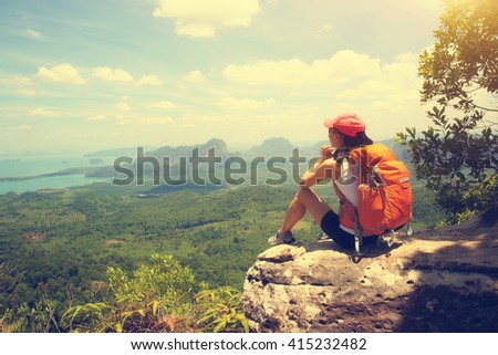 young woman hiker hiking at seaside mountain cliff