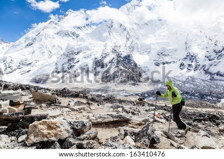 Young woman hiker hiking in Himalaya Mountains in Nepal over Mount Everest and Nuptse face with snow and avalanches.