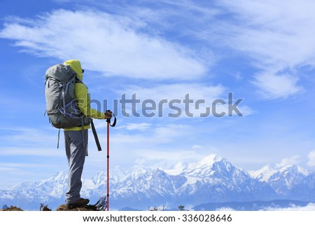 young woman hiker on mountain peak face the frozen mountain summits - stock photo