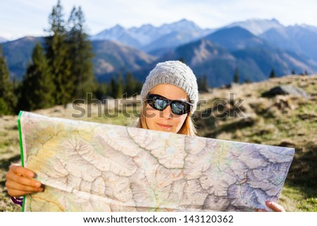 Young woman hiker reading map in mountains on hiking trip. Female trekker camping and planning in autumn nature, outdoors activity - stock photo