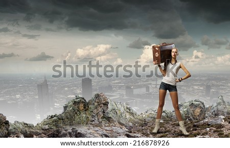 Young woman hiker walking with suitcase on shoulder
