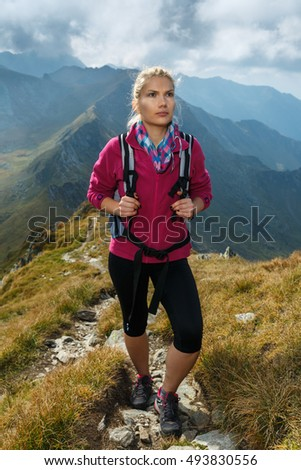 Young woman hiker with backpack walking a trail in rocky mountains