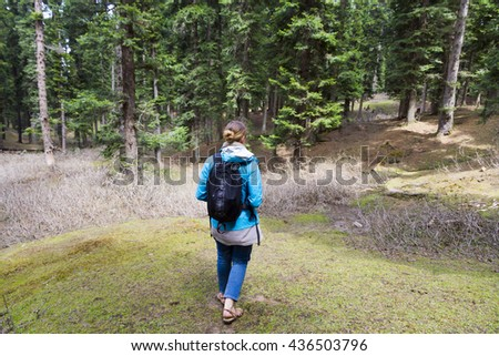 Young woman hiking in the mountain forests of Kashmir in the Indian Himalayas