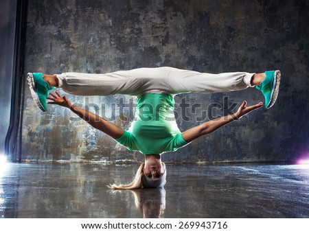Young woman hip-hop dancer standing on head on wall background. - stock photo