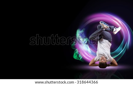 Young woman hip hop dancer with fire effect at background - stock photo