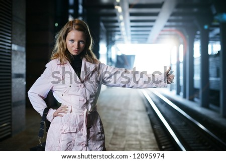 Young woman hitchhiking inside train station. Shallow DOF. - stock photo