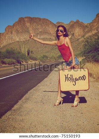 Young woman hitching a ride on lonely desert road - stock photo