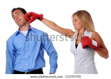 Young woman hitting man with boxing gloves - stock photo