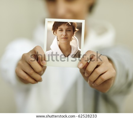 young woman hold self-portrait, selective focus on foreground (photo made by me) - stock photo
