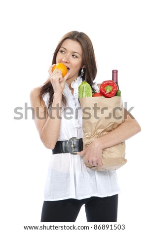 Young woman hold shopping paper bag full of vegetarian groceries, red pepper, salad, bottle of dry wine, asparagus, fresh organic tomatoes eating orange isolated on white background. - stock photo
