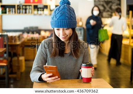Young woman hold with cellphone and enjoy her coffee - stock photo