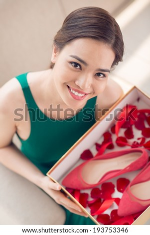 Young woman holding a box with red heels and rese petals, view from the top