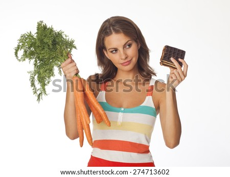 Young woman holding a cake and carrots,  against white background - stock photo