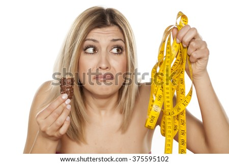 young woman holding a chocolate and a measuring tape - stock photo