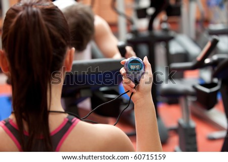 Young woman holding a chronometer and man doing physical exercise in a fitness center - stock photo