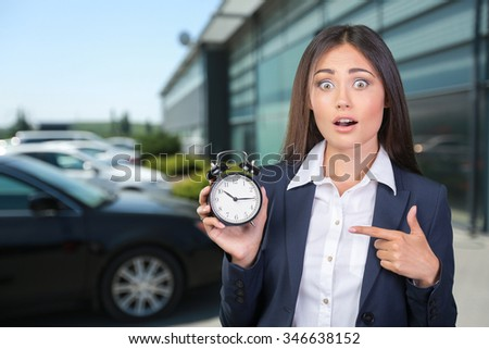 young woman holding a clock. time management concept. - stock photo