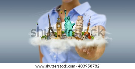 Young woman holding a cloud full of famous monuments of the world in his hands - stock photo