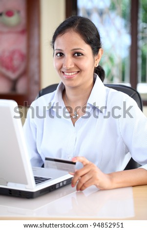 Young woman holding a credit card and doing on line shopping