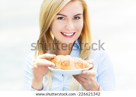 Young woman holding a croissant