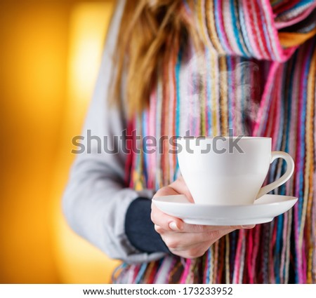 Young woman holding a cup of coffee in cafe. - stock photo