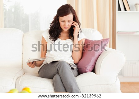 Young Woman holding a cup while reading a magazine in her living room