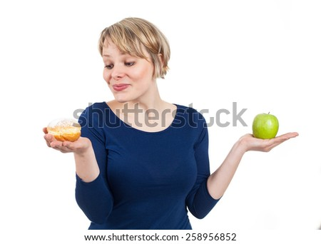 Young woman holding a donut and an apple, attracted by the donut, isolated on white - stock photo