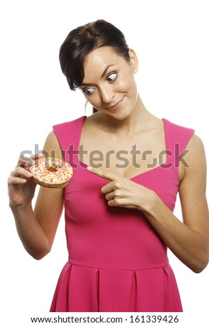 Young woman holding a doughnut looking guilty - stock photo