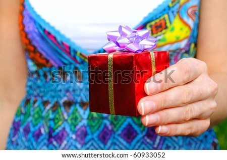 Young woman holding a gift in hand. outdoor. - stock photo