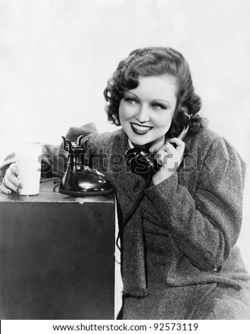 Young woman holding a glass of milk and talking on a rotary phone - stock photo