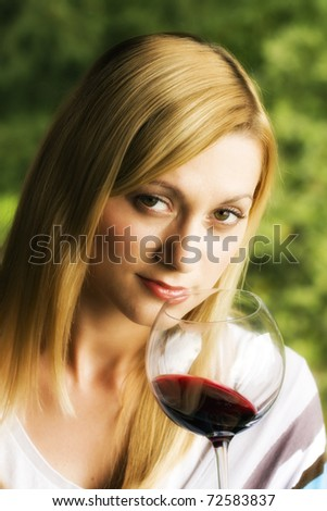 Young woman holding a glass of red wine. Lipstick marks on the glass.
