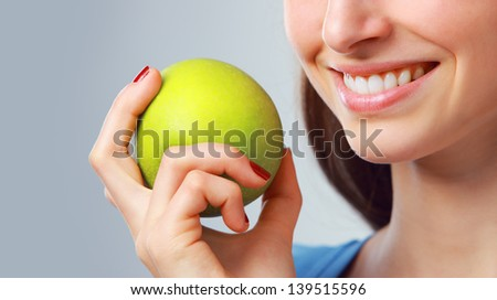 Young woman holding a green apple, close up - stock photo